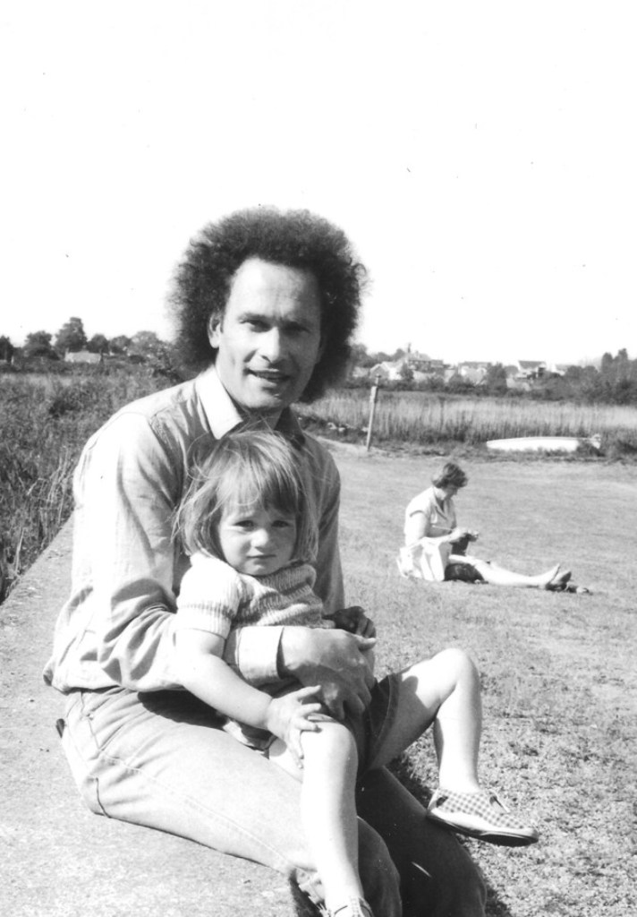 CM sitting on sea wall on beach with daughter Lucy