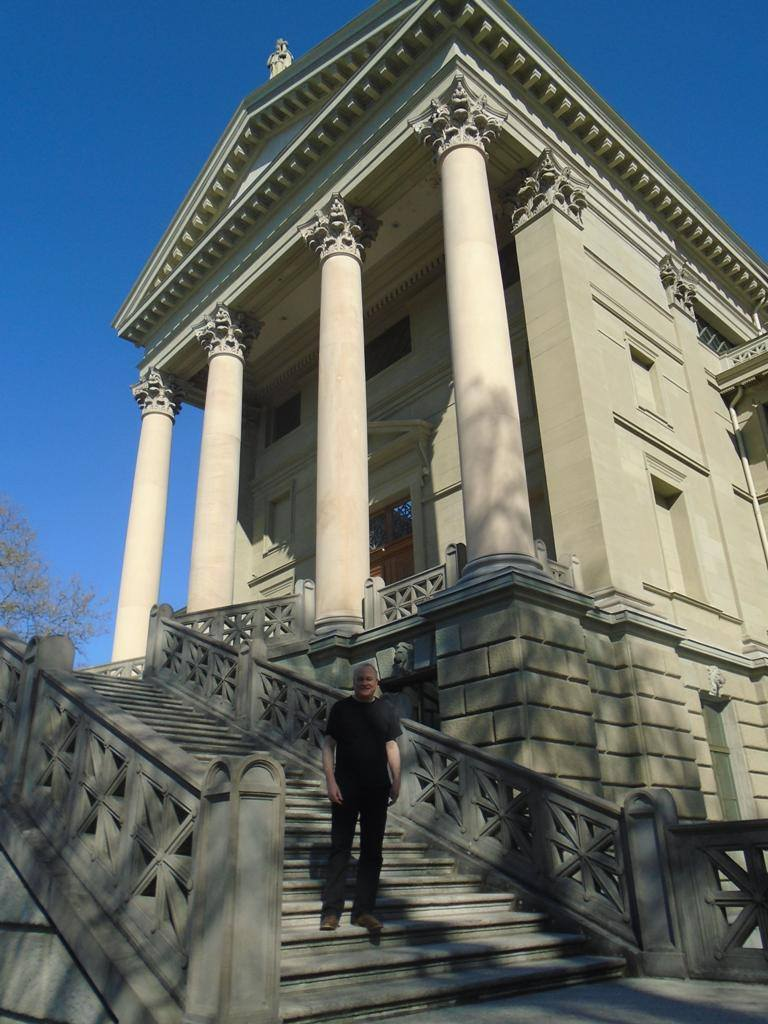 Colin Matthews standing on the steps of Stadthaus Winterthur (temple-like building with four pillars)