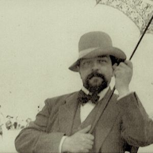 Black and white image of Debussy holding a parasol on a beach
