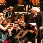 Leila Josefowicz playing the violin on stage very energetically, conducted by Simon Rattle wtih some members of the orchestra visible
