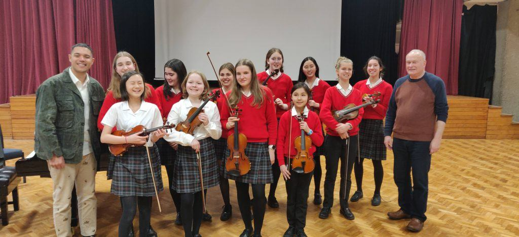 Group of young violinists in a concert hall with colin matthews