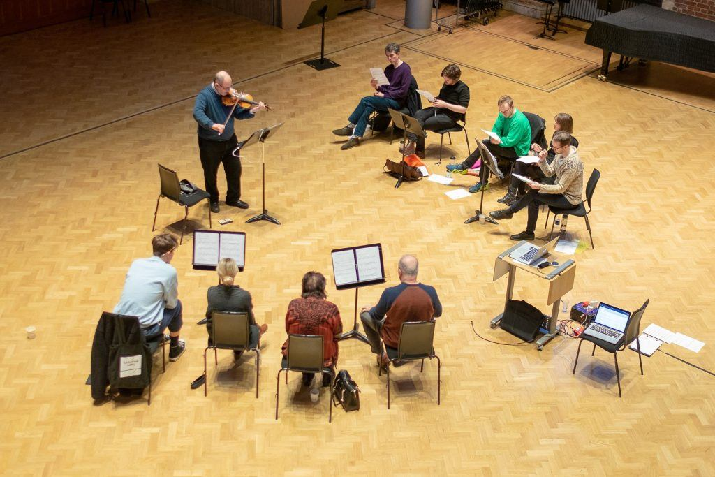 Group of musicians - violinist standing up and playing, composers aroun dhim in a circle looking at scores/notes