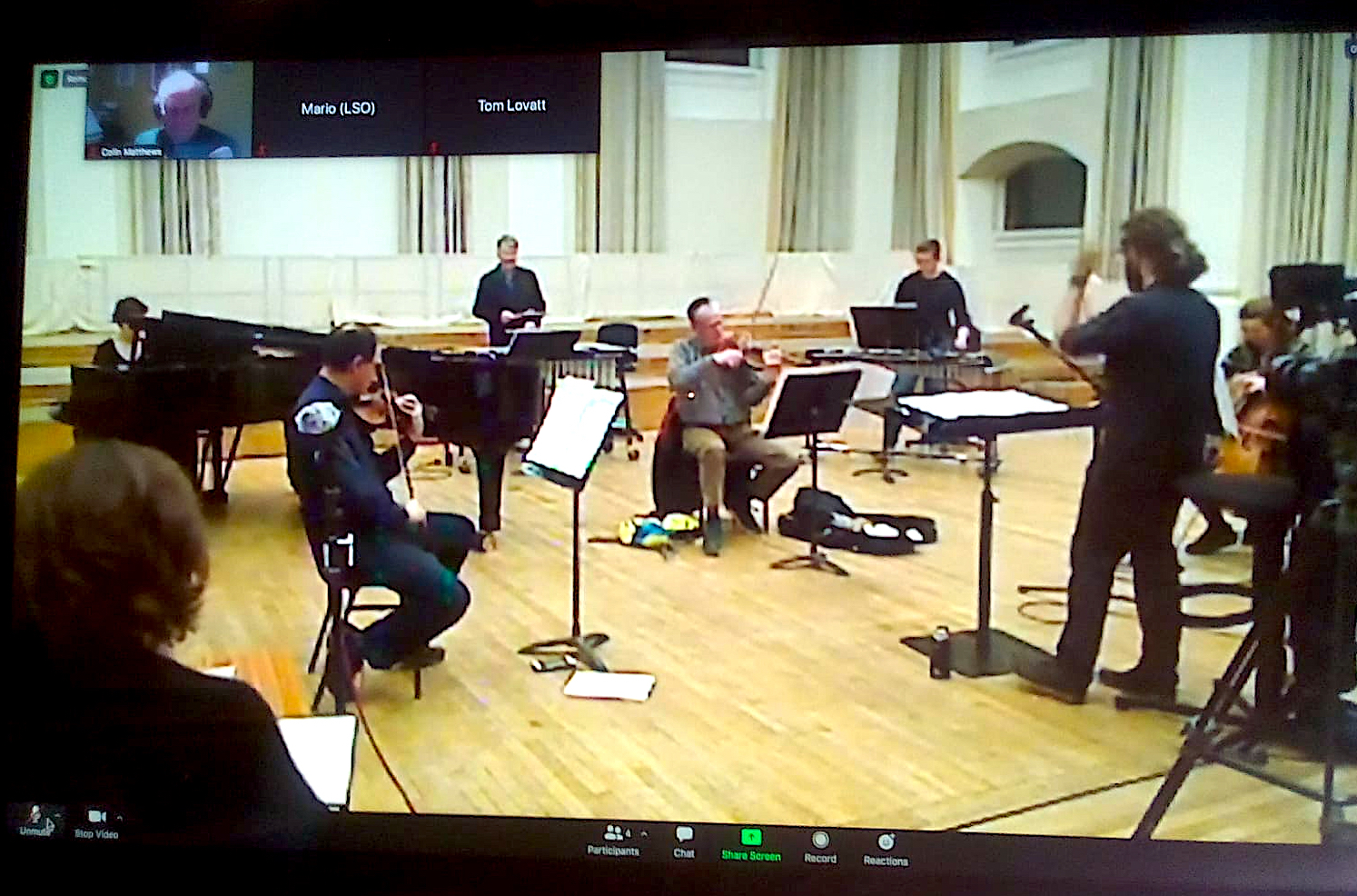 An ensemble of 6 (socially distanced) musicans plus conductor performing together; this is a screenshot on zoom and you can see Colin Matthews dialling in top left.
