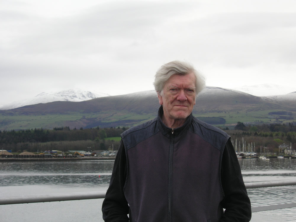 Tony Payne, standing in front of a lake and mountain view